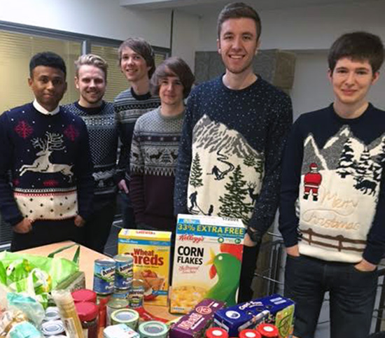 Webrevolve staff members in Christmas Jumpers next to Christmas food to donate