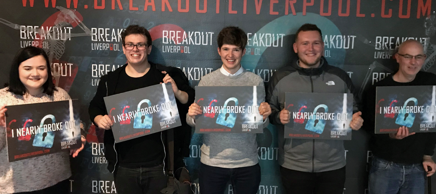 Webrevolve Team members holding signs of nearly broke out of Breakout Liverpool