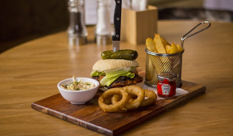 Burger, onion rings and chips on a wooden board
