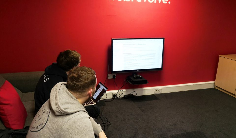 Two people viewing Magento 2.3 release notes in the Liverpool office